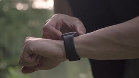 4k resolution closeup video of sports man making various gestures with a finger on a touch screen of a smart watch. Making various gestures with a finger on a stock footage