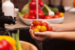 Making a vegetables salad, washing ingredients - cherry tomatoes Stock Photography
