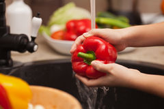 Making a vegetables salad, washing ingredients - red bell pepper Stock Photos