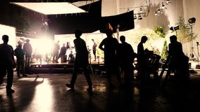 The making of video production and crew working. Behind the scenes or the making of film video production and movie crew team working in silhouette of camera Royalty Free Stock Photography