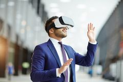 Making virtual report. Astonished businessman in suit making virtual presentation with help of vr goggles Royalty Free Stock Images