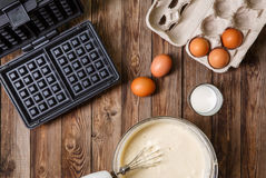 Making waffles at home - waffle iron, batter in bowl and ingredients - milk and eggs. Stock Photography