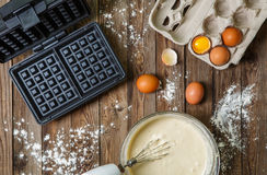 Making waffles at home - waffle iron, batter in bowl and ingredients - milk, eggs and flour. Royalty Free Stock Photos