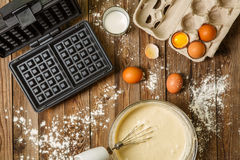 Making waffles at home - waffle iron, batter in bowl and ingredients - milk, eggs and flour. Stock Image