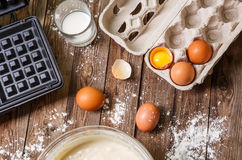Making waffles at home - waffle iron, batter in bowl and ingredients - milk, eggs and flour. Royalty Free Stock Photography