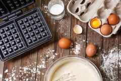 Making waffles at home - waffle iron, batter in bowl and ingredients - milk, eggs and flour. Royalty Free Stock Images