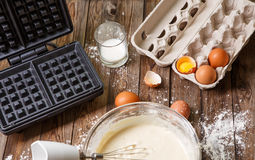 Making waffles at home - waffle iron, batter in bowl and ingredients - milk, eggs and flour. Stock Photos