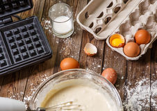 Making waffles at home - waffle iron, batter in bowl and ingredients - milk, eggs and flour. Royalty Free Stock Image