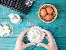 Making waffles at home - waffle iron, batter in bowl and ingredients - milk, eggs and flour. Stock Photo