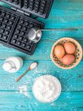 Making waffles at home - waffle iron, batter in bowl and ingredients - milk, eggs and flour. Stock Photography