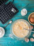 Making waffles at home - waffle iron, batter in bowl and ingredients - milk, eggs and flour. Royalty Free Stock Photo