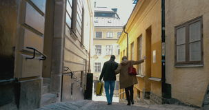 They making the way along ancient cobbled street. Steadicam shot of family couple of tourists walking down old cobbled street in Stockholm. Woman trying to step stock video