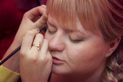 Making wedding make up. Young plump bride posing while making up close-up Stock Image