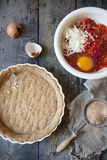 Making a wholemeal quiche with red peppers and cheese on ceramic mold on rustic table Royalty Free Stock Photo
