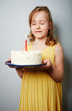 Making wish. Cute girl holding birthday cake with burning candle and making wish Royalty Free Stock Images
