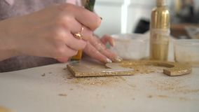 Making wooden decorations from wooden number five and golden glitter. Workplace.  stock video