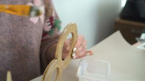 Making wooden decorations from wooden number eight and golden glitter. Workplace