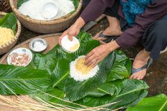 Making wrapping Chung Cake, the Vietnamese lunar new year Tet food outdoor with old woman hands and ingredients. Closed-up.  stock photos
