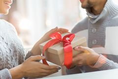 Making xmas surprise. Hands of young men giving xmas surprise in box with red ribbon to his girlfriend Royalty Free Stock Photo