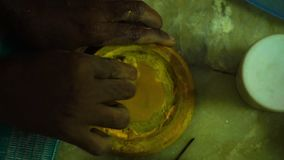 Making a yellow putty. A steady, aerial, close-up shot of a the hands of a man making a yellow putty
