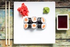 Makisushi sul piatto bianco Rotoli di sushi tradizionali di maki dei frutti di mare con i bastoncini Immagini Stock