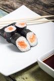 Makisushi on white plate. Seafood maki sushi rolls with chopsticks Stock Photo