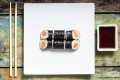 Makisushi on white plate. Seafood traditional maki sushi rolls with chopsticks Royalty Free Stock Photos