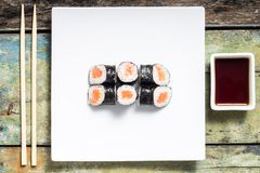 Makisushi on white plate. Seafood traditional maki sushi rolls with chopsticks Stock Image