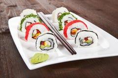 Makizushi. Rulli di sushi sulla zolla bianca. Immagini Stock
