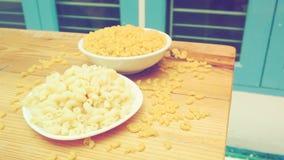 Makkaroni gekocht in der Platte und roh in der Schüssel mit rohem auf hölzernem Schreibtisch I Lizenzfreie Stockbilder