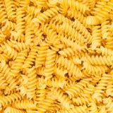 Makkaroni-Teigwarennahrungsmittelhintergrundbeschaffenheit des Italiener-Fusilli, Rotini oder Scroodle Stockfotografie