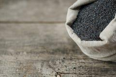 Makowi ziarna w burlap torbie na rocznika drewnianym szarym tle Smakowici, pożytecznie ziarna bogaci z i obraz stock