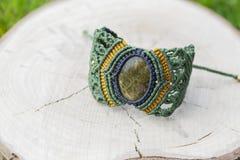 Makraméarmband med den naturliga mineraliska gemstonen på naturlig bakgrund arkivfoton
