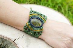 Makram?armband med den naturliga mineraliska gemstonen p? naturlig bakgrund royaltyfri foto