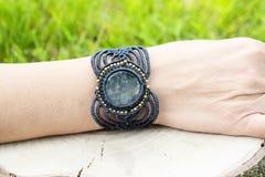 Makram?armband med den naturliga mineraliska gemstonen p? naturlig bakgrund royaltyfri fotografi