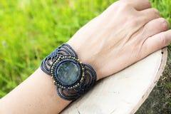 Makram?armband med den naturliga mineraliska gemstonen p? naturlig bakgrund arkivfoto