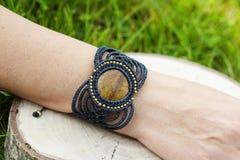 Makram?armband med den naturliga mineraliska gemstonen p? naturlig bakgrund arkivbild