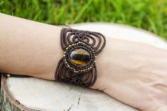 Makram?armband med den naturliga mineraliska gemstonen p? naturlig bakgrund arkivfoton
