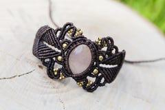 Makram?armband med den naturliga mineraliska gemstonen p? naturlig bakgrund fotografering för bildbyråer