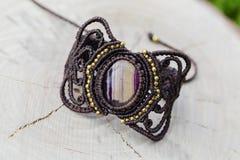 Makram?armband med den naturliga mineraliska gemstonen p? naturlig bakgrund royaltyfria foton