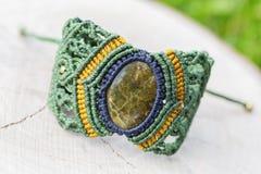 Makram?armband med den naturliga mineraliska gemstonen p? naturlig bakgrund royaltyfria bilder