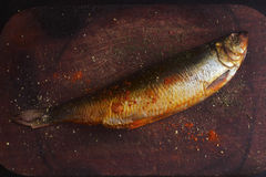 Makrill som rökas på en skärbräda med kryddor Arkivbilder