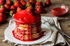 Makro amerikanische Pfannkuchen mit Erdbeermarmelade auf einem hölzernen Hintergrund Große Schärfentiefe stockfotos