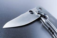 Makro av den liggande halva öppnade svaga militära kniven för A på mörkerjordning Royaltyfria Foton
