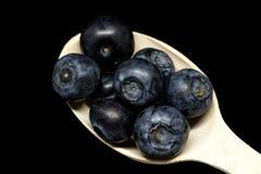 Makro av en träsked mycket av mogna blåbär på den svarta bakgrunden Nya mogna saftiga blåbär arkivfoton