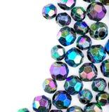 Makro av facted skinande metalliska pärlor mot vit Arkivbild