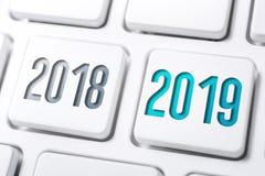 Makro av 2 knappar med året 2018 och 2019 på det vita tangentbordet royaltyfri foto