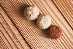 Makro- Biali i dojni czekoladowi cukierki na lekkim drewnianym tle zdjęcie royalty free