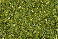 Makro der getrockneten Hintergrundbeschaffenheit des grünen Tees Stockfoto