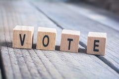 Makro der Wort-Abstimmung gebildet durch Holzklötze auf einem Bretterboden Lizenzfreies Stockfoto